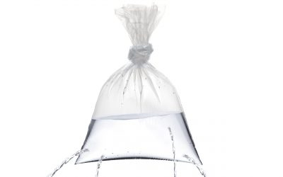 A plastic bag with holes, being filled, but the water is leaking out the holes isolated on white background